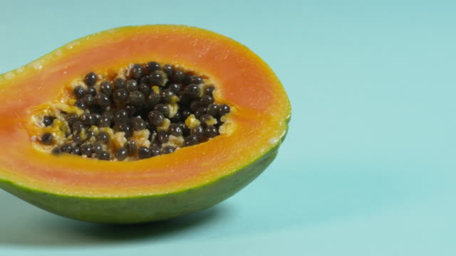 pan right across, then pan left across, a halved papaya on a plain blue background. - papaya stock videos & royalty-free footage