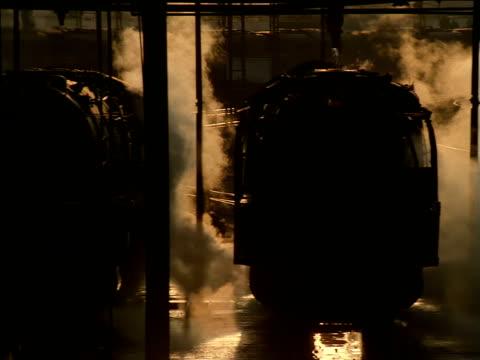 vídeos de stock, filmes e b-roll de pan right across three stationary steam trains side by side in train yard - imagem tonalizada