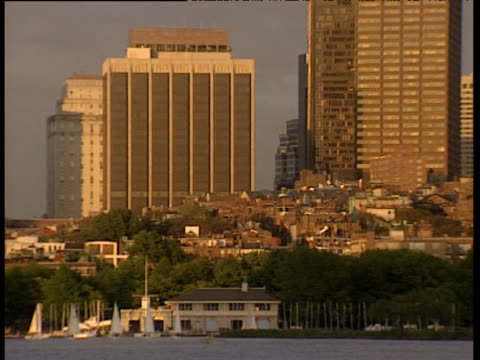 pan right along boston skyline at dusk as sunlight reflects off skyscrapers and old buildings with river and boats in foreground - boston massachusetts stock videos & royalty-free footage