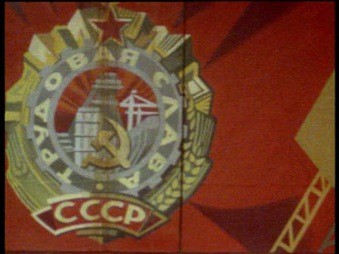 pan right along communist workers mural in russian factory - ex unione sovietica video stock e b–roll