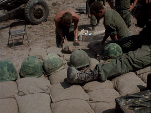 pan right along green helmets resting on sandbags at army camp tilt up to soldier playing harmonica with american troops packing sandbags in... - 1964 stock videos & royalty-free footage
