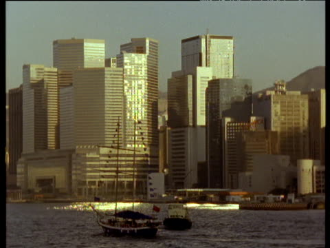 pan right along harbor with boats in foreground and skyscrapers behind - 1986 stock videos and b-roll footage