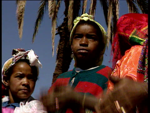 pan right along line of villagers wearing colourful local dress dancing and clapping - dress stock videos and b-roll footage