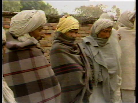 vidéos et rushes de pan right along queue of male voters wrapped in blankets outside polling station during general election uttar pradesh; dec 84 - coiffe traditionnelle