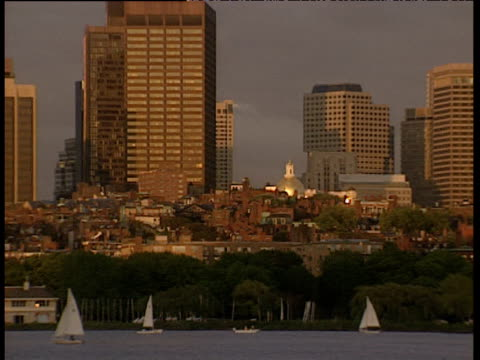 vidéos et rushes de pan right along red brick buildings of boston skyline. dusky orange sun shines brightly on skyscrapers and other tall buildings. sailing boats on river in foreground - boston
