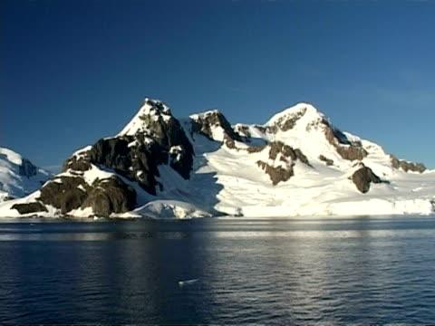 wa pan right along snowy mountain coastline, sea water foreground, blue sky, sunny, antarctic peninsula - antarctic peninsula stock videos & royalty-free footage