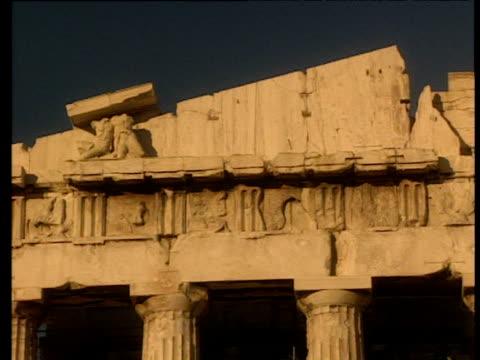 vídeos de stock, filmes e b-roll de pan right along stone carvings in pediment of the parthenon under dark blue sky athens - partenão acrópole