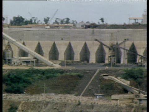 pan right along wall of itaipu dam under construction brazil 1980's - erezione video stock e b–roll