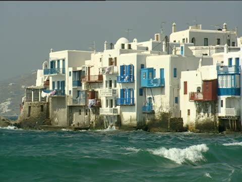 vidéos et rushes de pan right along whitewashed houses as waves splash against them at high tide - style des années 2000