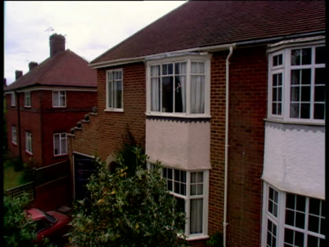 pan right and crane down over line of houses on suburban estate to trees and brick wall. - erkerfenster stock-videos und b-roll-filmmaterial