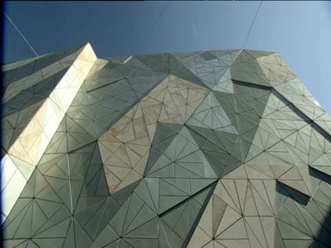 Pan right and tilt down metal and glass irregularly shaped exterior of Federation Square building to cafe umbrellas Melbourne