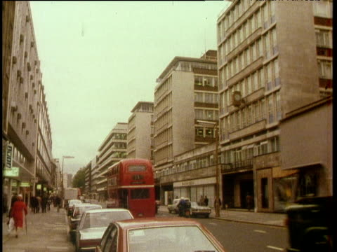 pan right and tilt up to michael house on busy oxford street london; 1970's - dubbeldäckarbuss bildbanksvideor och videomaterial från bakom kulisserna