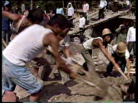 pan right and zoom in to construction workers pushing rubble off board pyongyang; 1988 - north korea stock videos & royalty-free footage