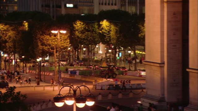 vidéos et rushes de pan right and zoom out from pedestrians on place de l'etoile to view of arc de triomphe illuminated at night / paris, france - arc élément architectural