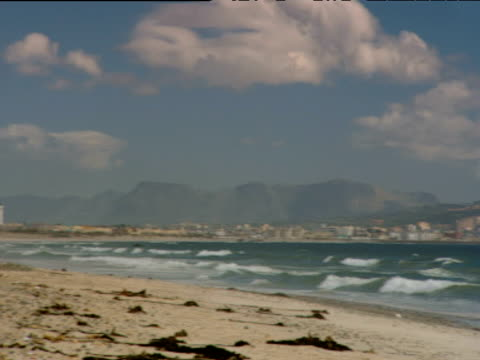 Pan right and zoom out over Table Mountain with layer of cloud resting on top waves lap onto beach in foreground