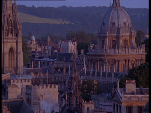 pan right around impressive buildings of oxford university at sunset including turret and dome structures on roof - oxford england stock videos and b-roll footage