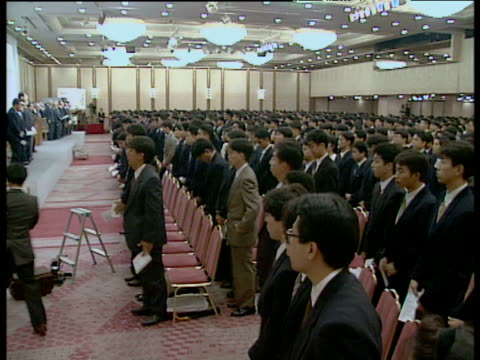 Pan right around room full of Japanese businessmen and women wearing suits all stand up and bow heads in unison Japan