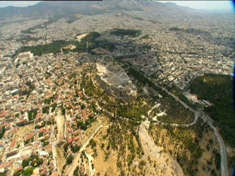 Pan right around the Acropolis perched high on hilltop Athens spreads into distance behind