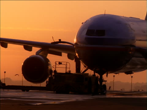 vidéos et rushes de pan right as aircraft is refuelled on runway at sunset - faire le plein d'essence