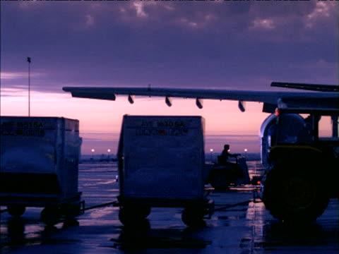 pan right as airport baggage vehicle pulls carts along runway passing aeroplane - towing stock videos & royalty-free footage