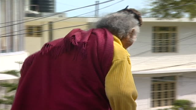 pan right as an elderly buddhist man dressed in a chuba walks down a road as a van speeds by and honks. thousands of tibetan exiles live in... - long hair stock videos & royalty-free footage