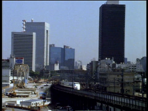 pan right as bullet train travels on raised tracks through city japan - 1980~1989年点の映像素材/bロール