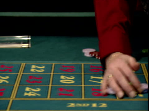 pan right as croupier's hands sweep coloured gambling chips off table and down chute - casino stock videos & royalty-free footage