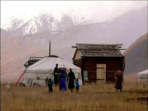 stockvideo's en b-roll-footage met pan right as family wander towards traditional darhad nomadic settlement darhad valley mongolia - mongolië