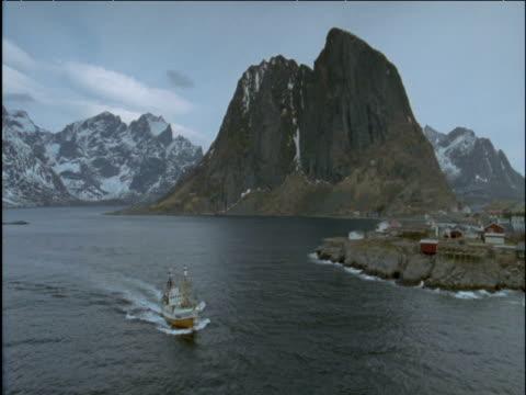vídeos de stock, filmes e b-roll de pan right as fishing boat enters mountainous fjord - indústria da pesca