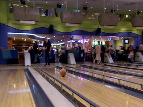 pan right as man bowls ball down lane and scores strike in ten-pin bowling - bowling ball stock videos & royalty-free footage