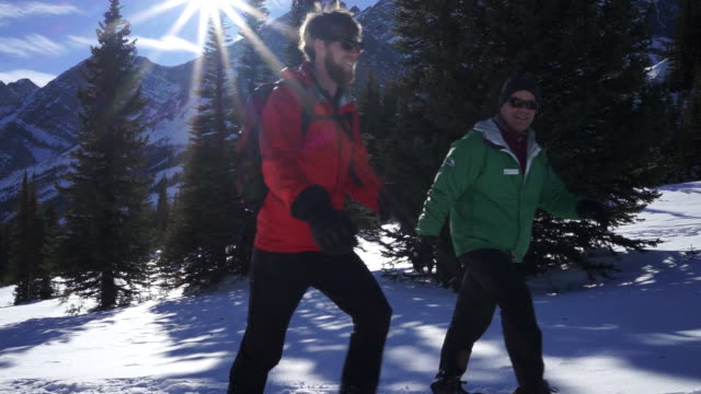 Pan right as mature man and young man talk and smile as they walk on snowshoes