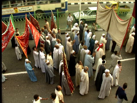 stockvideo's en b-roll-footage met pan right as muslim men carry banners in street procession during maulid festival celebrating birth of prophet mohammed cairo - kleding
