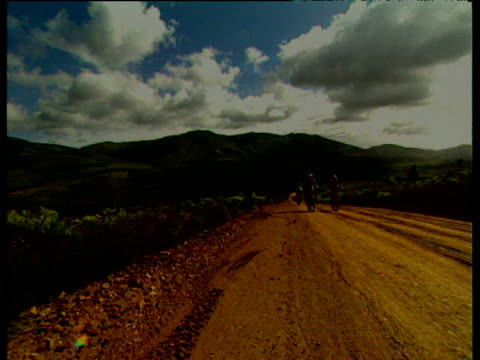 pan right as near silhouetted cyclists slowly make way up steep dusty gravel road, rolling hills in background under cloudy blue sky, cape epic 2004,... - steep stock videos & royalty-free footage