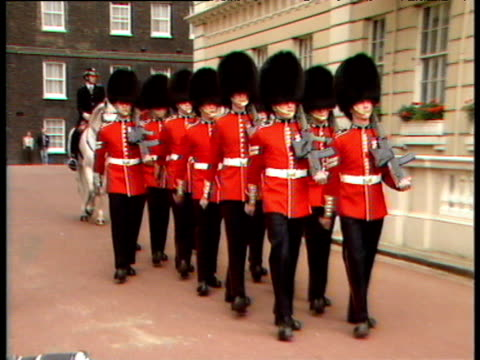 pan right as soldiers from grenadier regiment of foot guards and welsh regiment of foot guards march down road followed by mounted policeman past camera queen mother's 88th birthday celebrations clarence house; 04 aug 88 - 近衛兵点の映像素材/bロール
