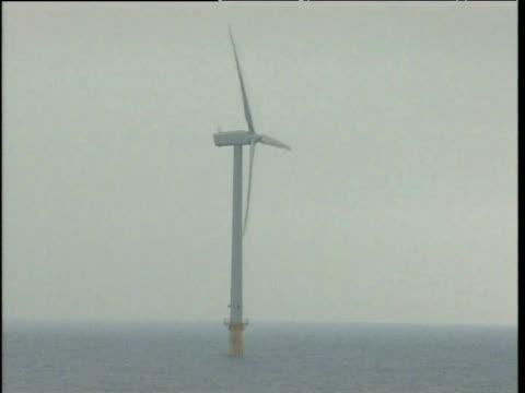 Pan right between wind turbines in sea UK
