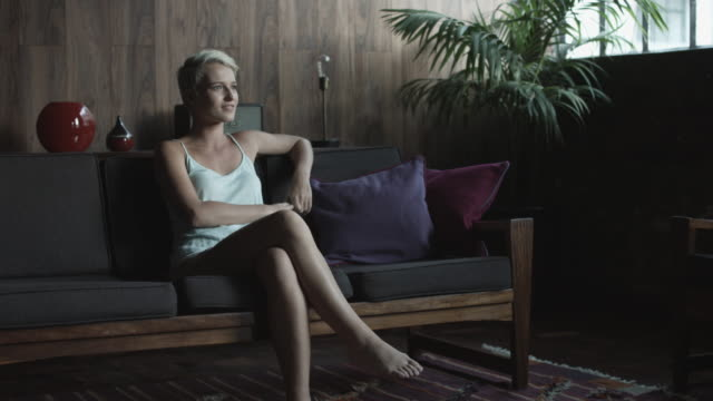 pan right, blonde woman sits on couch - kamisol stock-videos und b-roll-filmmaterial