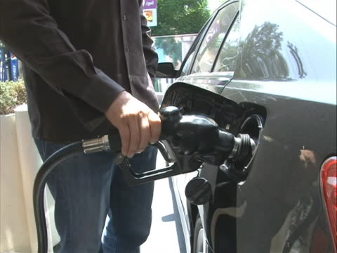 stockvideo's en b-roll-footage met pan right broll shot of a man placing a fuel pump into his car at a gas station high prices of gasoline put further strain on us citizens who... - benzineprijzen