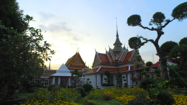 pan right: buddhist building with colorful garden in front on clear day - bangkok, thailand - パン効果点の映像素材/bロール