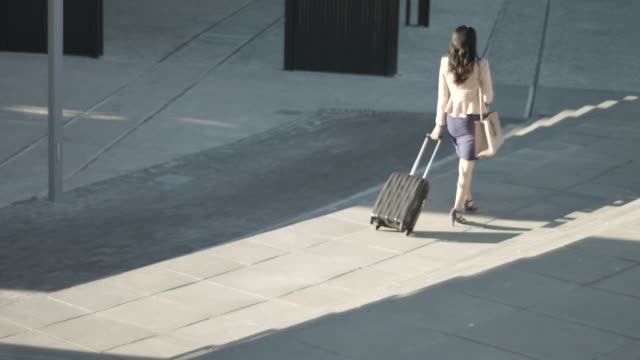 pan right, businesswoman with suitcase - full length stock videos & royalty-free footage
