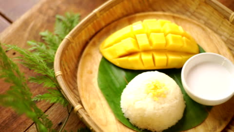 cu pan right camera : thai mango with sticky rice served on banana leaf in basket, thai style dessert. - mango fruit stock videos & royalty-free footage