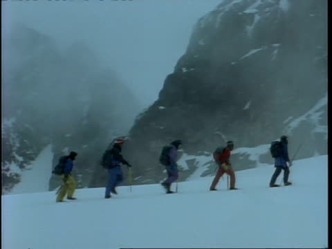 ms pan right, following people walking across snow, against mountains shrouded in fog, rwenzori mountains, uganda - hoch allgemeine beschaffenheit stock-videos und b-roll-filmmaterial