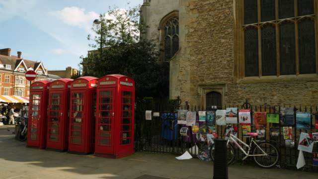 vídeos y material grabado en eventos de stock de pan right from a row of stereotypically british phone boxes to notices outside the university church of st mary the great, cambridge, uk. - cabina de teléfono