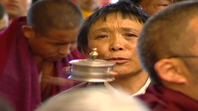 pan right from a worshipper spinning a prayer wheel to a tibetan buddhist monk listening to a sermon by hh dalai lama. the 14th dalai lama lives in... - worshipper stock videos & royalty-free footage