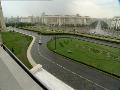 Pan right from balcony of Ceaucescu's Palace to wide roads and green traffic island Unirii Boulevard stretches away in distance Bucharest