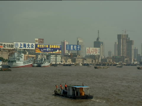 pan right from billboards around boats floating in shanghai port skyscrapers and construction work in background - erektion stock-videos und b-roll-filmmaterial