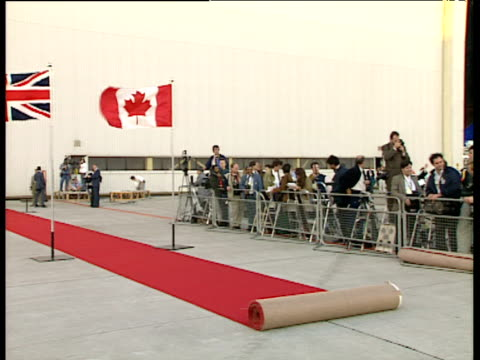 Pan right from Canada and Union Jack flags flanking partially unrolled red carpet to bank of photographers at Toronto airport Canada Royal Tour; Oct 91