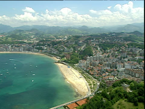 Pan right from deep green sea and busy beach to town of Biarritz from top of hill Southern France