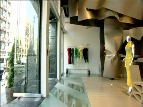 stockvideo's en b-roll-footage met pan right from entrance to interior of modern boutique revealing mannequins wearing bright coloured dresses new york - jaar 2000 stijl