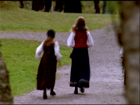 pan right from girls in traditional norwegian dress walking along path away from camera to thatched building, norway - school children stock videos & royalty-free footage