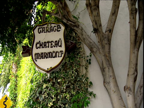 Pan right from hotel garage sign to red 4x4 driving out Hotel Chateau Marmont Sunset Strip Los Angeles